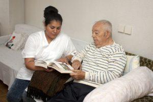 Femme aidant une personne agée à lire assis sur le canapé