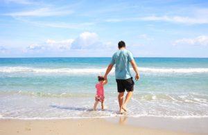 Père donnant sa fille par la main sur la plage